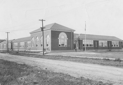 Somewhat later picture of Margaret Scott School with landscaping and flagpole