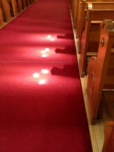 Trinity of light in aisle of a church