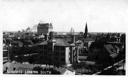 Classic Winnipeg cityscape: Carlton School, the 1903 version, is in the foreground. Notice the spiral fire escape slide on right side of building. To the right is the spire of St Mary's Cathedral and the Fort Garry Hotel in the left distance.